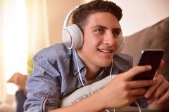 Música cantante y que escucha adolescente con la cara de mentira de los auriculares abajo Imágenes de archivo libres de regalías