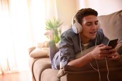 Música cantante y que escucha adolescente con la cara de mentira de los auriculares abajo Fotos de archivo libres de regalías