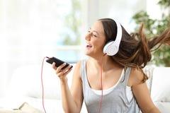 Música cantante y que escucha de la muchacha en un sofá Imagenes de archivo