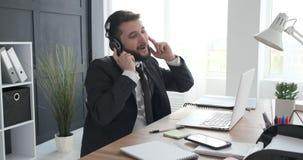 Música cantante y que escucha del hombre de negocios en el trabajo almacen de metraje de vídeo
