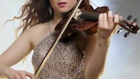 Música clásica, hembra que sorprende en el vestido brillante que juega en el violín en niebla almacen de video