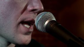 Música considerável do canto do músico do retrato no microfone no consert da rocha na fase filme