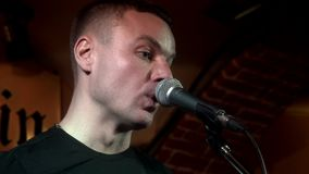 Música considerável do canto do músico do retrato no microfone no consert da rocha na fase video estoque