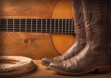 Música country americana con los zapatos de la guitarra y del vaquero en el texto de madera Imágenes de archivo libres de regalías