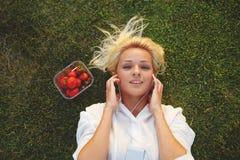 Música de apreciação fêmea atrativa ao descansar na grama verde após dar uma volta imagem de stock