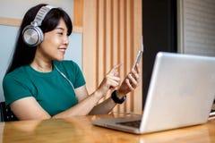 Música de apreciação fêmea nova através dos fones de ouvido novos com a qualidade do som da aplicação do smartphone, sorrindo foto de stock royalty free