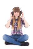 Música de assento e de escuta do adolescente bonito com fones de ouvido Fotos de Stock Royalty Free