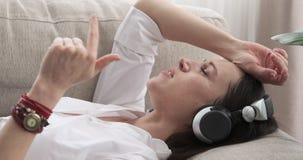 Música de canto e de escuta da mulher em fones de ouvido ao encontrar-se no sofá vídeos de arquivo