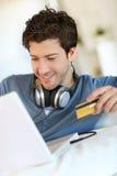 Música de compra sonriente joven del hombre en Internet Foto de archivo libre de regalías