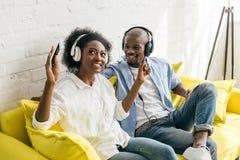 música de escuta afro-americano nos fones de ouvido ao descansar no sofá fotografia de stock