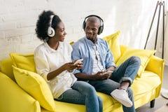música de escuta afro-americano nos fones de ouvido com smartphones ao descansar no sofá fotos de stock