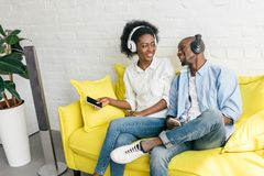 música de escuta afro-americano de sorriso nos fones de ouvido com smartphones ao descansar no sofá imagem de stock