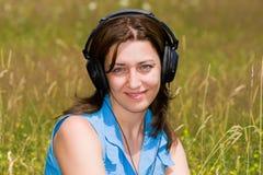 Música de escuta atrativa da mulher nova ao ar livre Foto de Stock Royalty Free
