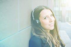 Música de escuta autêntica nova da mulher de negócio ao móbil Imagem de Stock Royalty Free