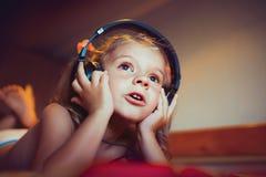 Música de escuta da criança bonito que encontra-se na cama Imagem de Stock