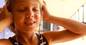 Música de escuta da estudante nos fones de ouvido 4k video estoque