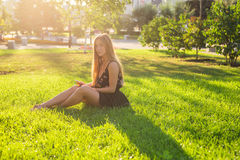 Música de escuta da jovem mulher bonita no parque Fotografia de Stock