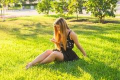 Música de escuta da jovem mulher bonita no parque Imagem de Stock