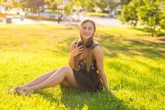 Música de escuta da jovem mulher bonita no parque Fotografia de Stock Royalty Free