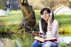 Música de escuta da jovem mulher com sua tabuleta em um parque do outono Foto de Stock Royalty Free