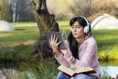 Música de escuta da jovem mulher de uma tabuleta em um parque do outono Fotos de Stock