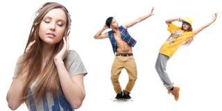 Música de escuta da jovem mulher e dois dançarinos no fundo Fotografia de Stock Royalty Free