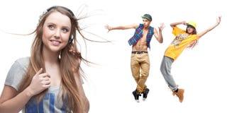 Música de escuta da jovem mulher e dois dançarinos no fundo Imagens de Stock Royalty Free