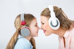 Música de escuta da mãe e da filha com os fones de ouvido no estúdio imagem de stock royalty free