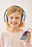 Música de escuta da menina bonito em fones de ouvido Fotografia de Stock