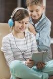 Música de escuta da menina bonito na tabuleta digital quando irmão que está atrás dela em casa foto de stock royalty free