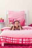 Música de escuta da menina com auscultadores Fotografia de Stock Royalty Free