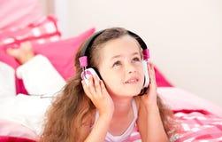 Música de escuta da menina com auscultadores Fotografia de Stock