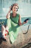 Música de escuta da menina da forma do moderno exterior Imagem de Stock