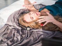 Música de escuta da menina feliz usando fones de ouvido e cantando na cama em casa Imagem de Stock