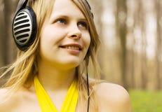 Música de escuta da menina nos auscultadores. Natureza da mola imagens de stock royalty free