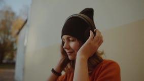Música de escuta da moça bonito nos fones de ouvido e na dança, estilo urbano, moderno à moda adolescente no chapéu negro para es filme