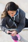 Música de escuta da mulher alegre da aptidão no smartphone Foto de Stock Royalty Free