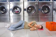 Música de escuta da mulher ao descansar na lavanderia imagens de stock