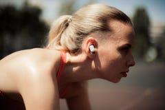 Música de escuta da mulher da aptidão nos fones de ouvido sem fio, fazendo exercícios do exercício na rua Fones de ouvido de Blue Fotos de Stock