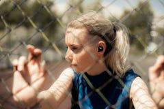 Música de escuta da mulher da aptidão nos fones de ouvido sem fio, fazendo exercícios do exercício na rua Fones de ouvido de Blue Imagem de Stock