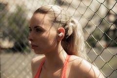 Música de escuta da mulher da aptidão nos fones de ouvido sem fio, fazendo exercícios do exercício na rua Fones de ouvido de Blue Imagens de Stock Royalty Free