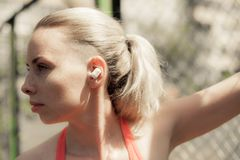 Música de escuta da mulher da aptidão nos fones de ouvido sem fio, fazendo exercícios do exercício na rua Fones de ouvido de Blue Fotos de Stock Royalty Free