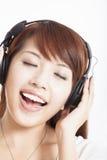 Música de escuta da mulher asiática Imagens de Stock