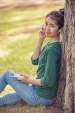 Música de escuta da mulher asiática bonita Fotografia de Stock