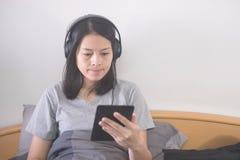 Música de escuta da mulher asiática bonita com fones de ouvido e eBook da leitura com os e-leitores que relaxam na cama imagem de stock royalty free