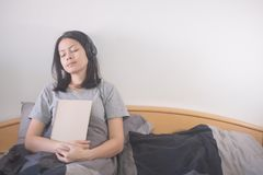 Música de escuta da mulher asiática bonita com o fones de ouvido e o livro de leitura que relaxam na cama foto de stock royalty free