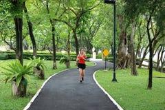 Música de escuta da mulher asiática saudável do corredor da aptidão e exercício running no parque natural imagem de stock royalty free