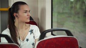 A música de escuta da mulher bonita nos fones de ouvido no trem da equitação do smartphone, menina bonita monta um ônibus da cida vídeos de arquivo