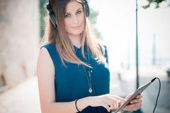 Música de escuta da mulher bonita nova do moderno Imagens de Stock