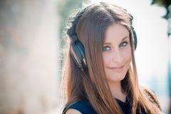 Música de escuta da mulher bonita nova do moderno Fotografia de Stock Royalty Free